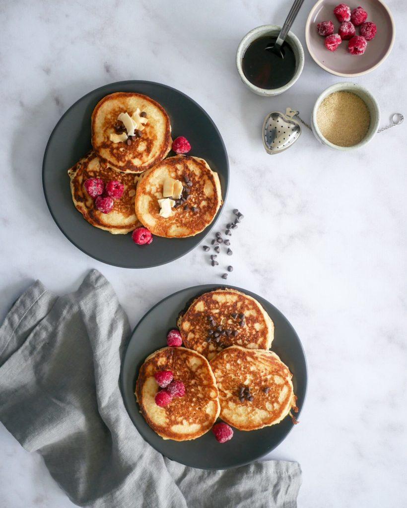 Pancakes vegans accompagnés de pépites de chocolat, de framboises et de copeaux de noix de coco.